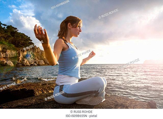 Woman sitting on rocks by sea meditating, Palma de Mallorca, Islas Baleares, Spain, Europe