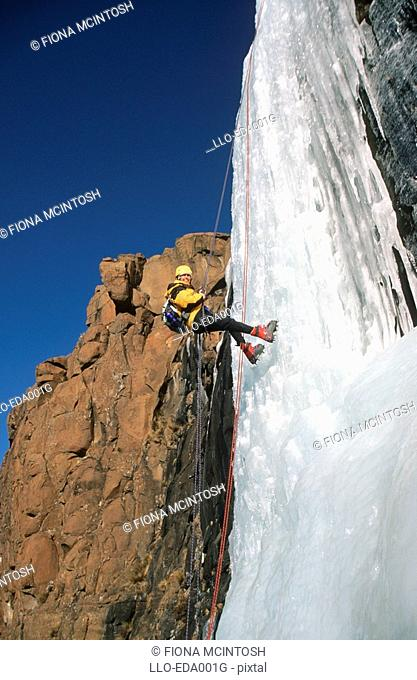 Woman Abseiling Down a Frozen Waterfall  Giants Castle Nature Reserve, Drakensberg, Freestate Province, South Africa