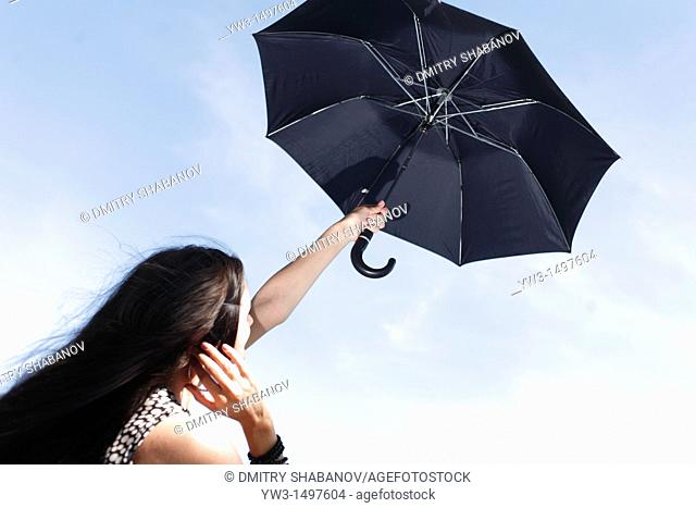 25 year old woman outdoors with umbrella against sky