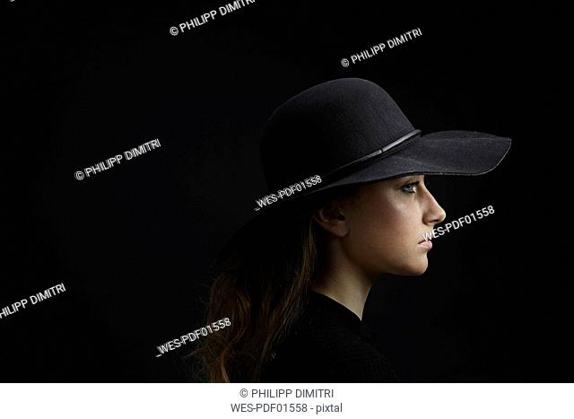 Profile of sad young woman wearing black hat against black background