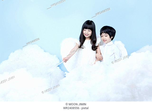 Boy and a girl in angel costume looking down in the background representing heaven