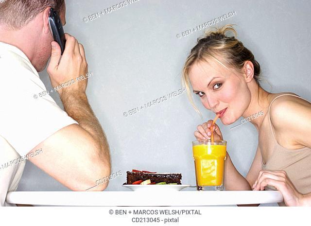 Woman drinking orange juice with man talking mobile phone