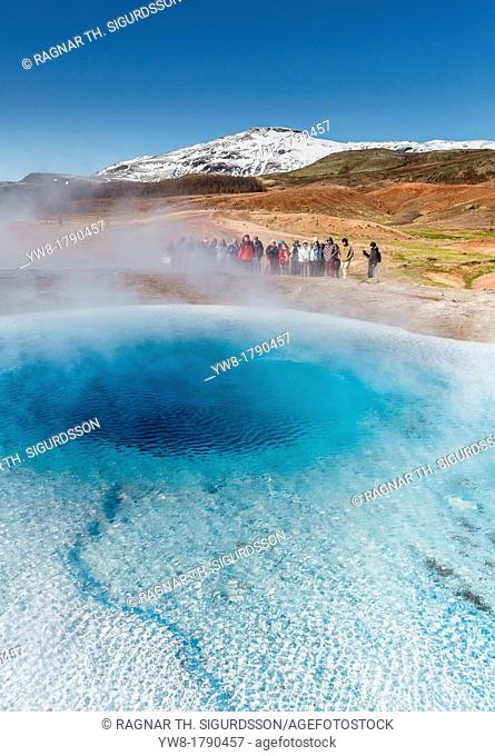 Tourist waiting for Strokkur geyser to erupt, Iceland Strokkur is a fountain geyser in the geothermal area beside the Hvita River  It is one of Iceland's most...