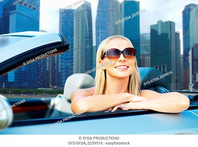 woman in convertible car over singapore city