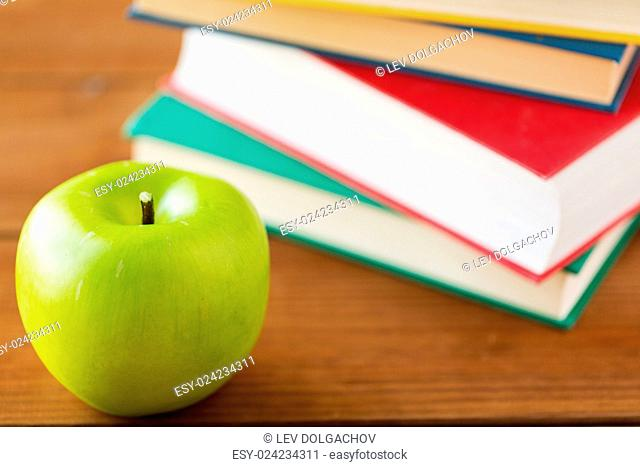 education, school, literature, reading and knowledge concept - close up of books and green apple on wooden table