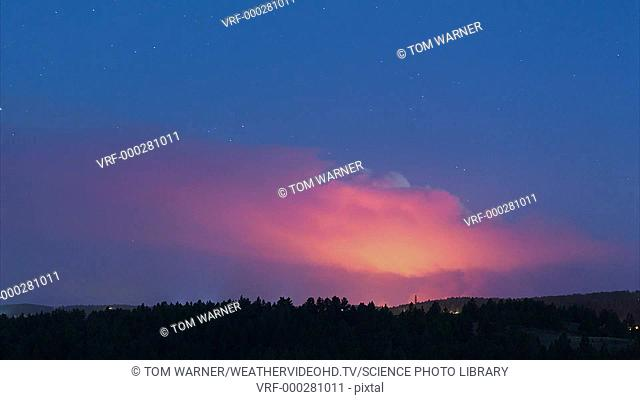 Timelapse footage of a forest fire at night, illuminating its huge smoke plume. The rising smoke reveals the different wind directions at different levels