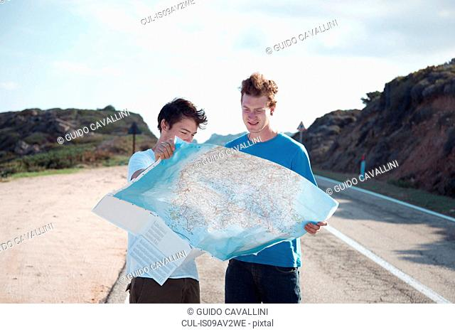 Young men standing on road looking at map smiling, Costa Smeralda, Sardinia, Italy