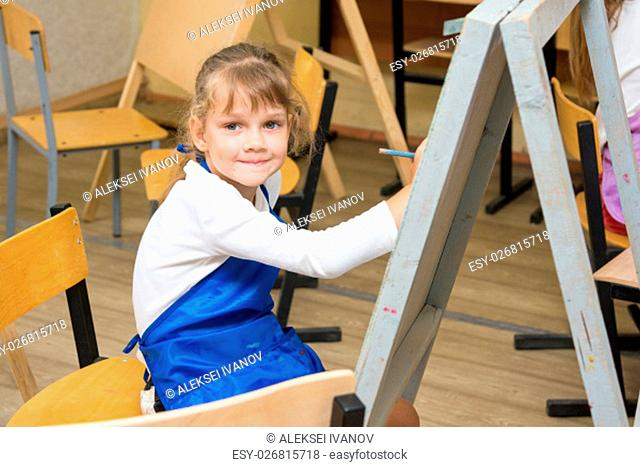 Girl draws pencil on an easel to draw a lesson and looked into the frame