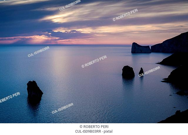 High angle silhouetted view of rock formations and cliffs at dusk, Masua, Italy