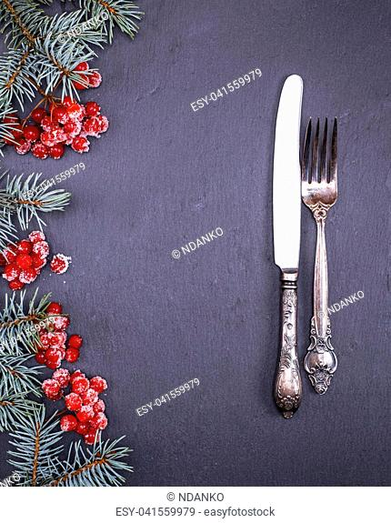 iron vintage fork and knife on a black background, decorated with a branch of spruce and clusters of viburnum, empty space in the middle