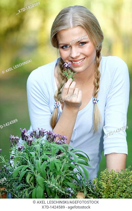 blonde woman with basket filled with fresh herbs in garden