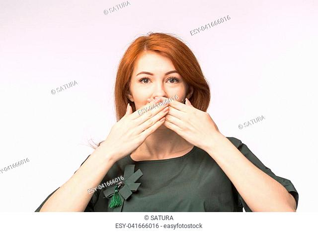 Readhead woman with palms over mouth on white background