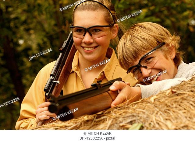 Teenage Boy And Girl Squirrel Hunting With Pellet Gun