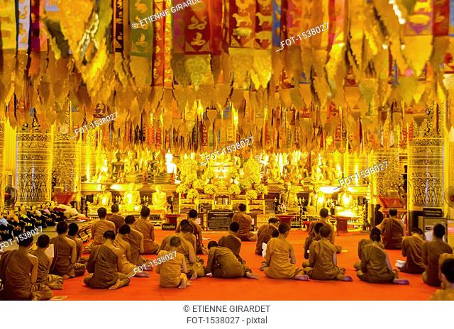 Rear view of monks sitting in Wat Chedi Luang temple