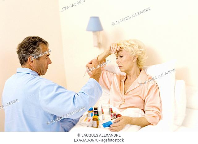 Senior woman in bed getting medication from senior man