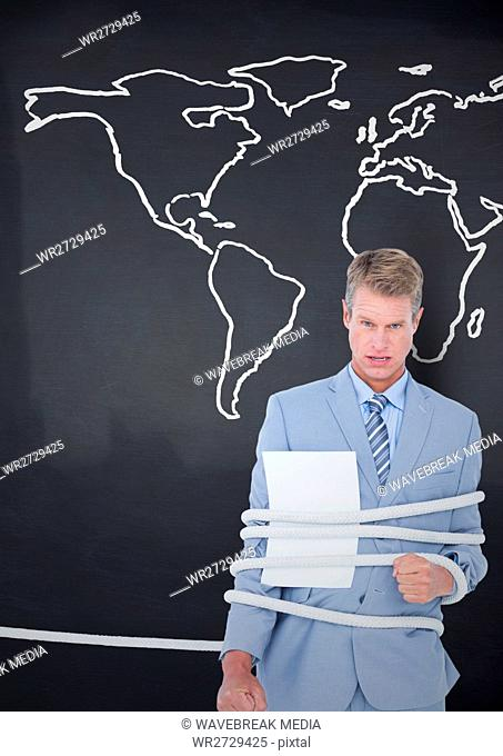 Businessman tied up in rope against world map