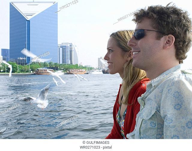 Couple watching sea gulls on Abra at Dubai Creek, United Arab Emirates