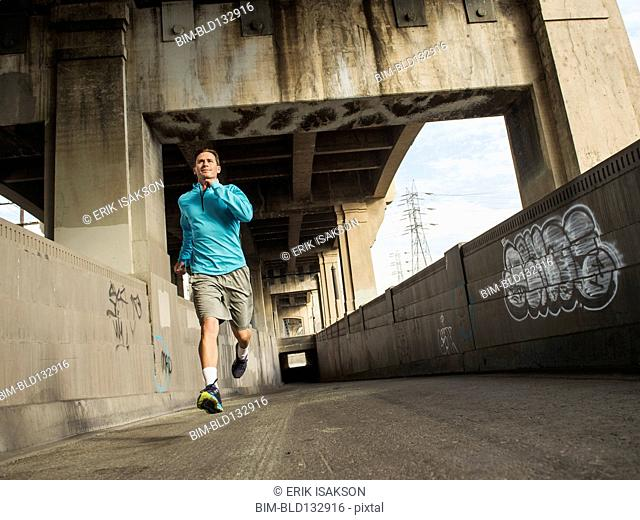 Caucasian man running in urban tunnel