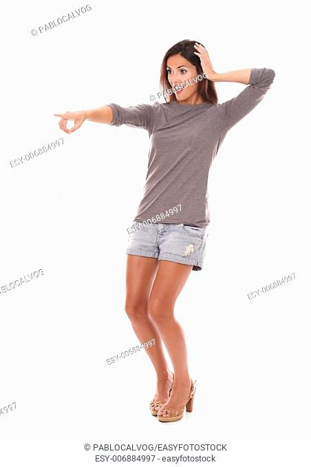 Happy latin female with finger pointing to her right on full length while smiling and standing in white background - copyspace