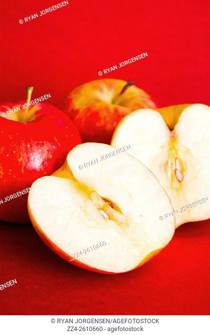Food photograph of red apples and slices on red card background. Apple still life