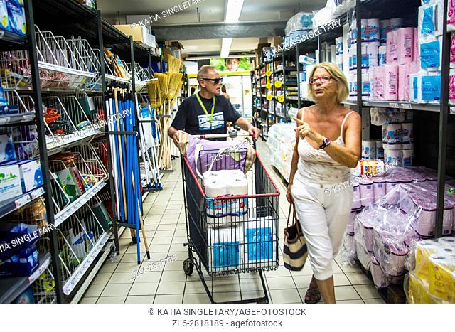 Mature retired senor caucasian woman doing her grocery shopping on vacation