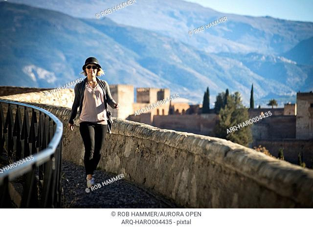 A girl walks down a pathway near the Alhambra in Granada, Spain on a sunny day