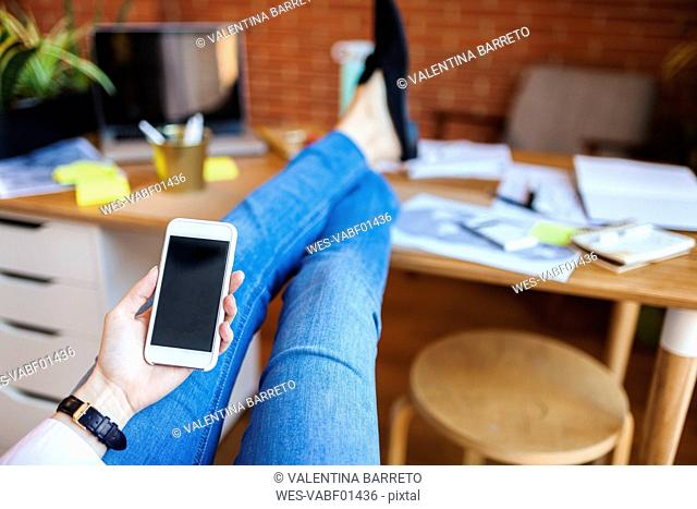 Close-up of businesswoman holding cell phone with feet on table in office