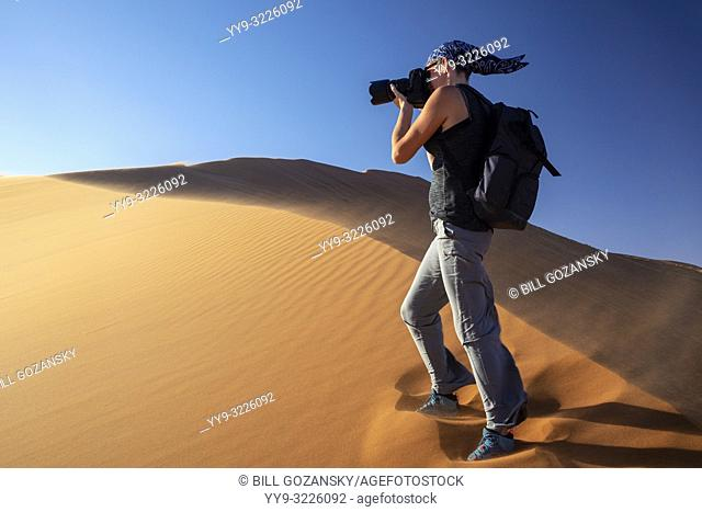Woman photographing on Elim Dune in Namib-Naukluft National Park, Namibia, Africa
