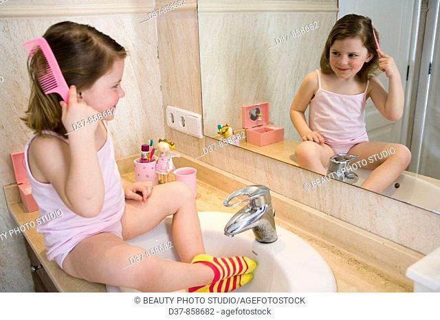 Little girl combing her hair in the bathroom
