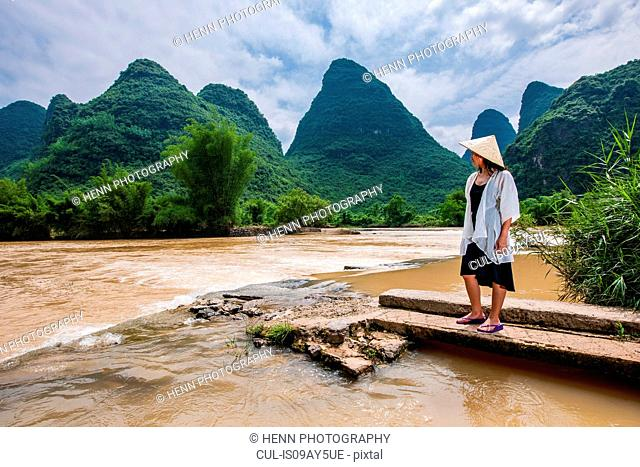 Woman with traditional straw hat looking at the flooded Yulong river in Guangxi, China