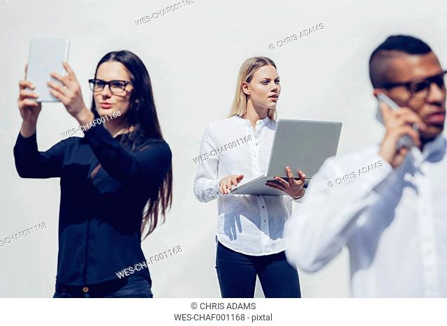 Three stylish young people with mini tablet, smartphone and laptop in front of white background