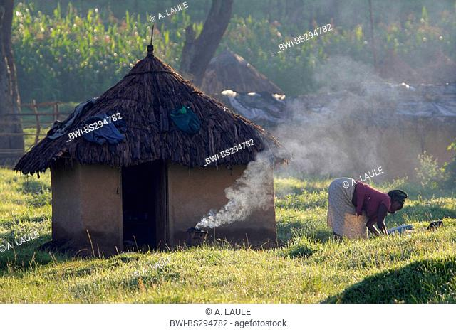 african woman working in front of her mud house, Uganda, Kisoro