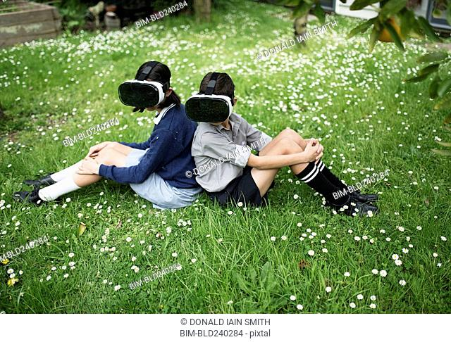 Mixed Race brother and sister sitting in grass wearing virtual reality goggles