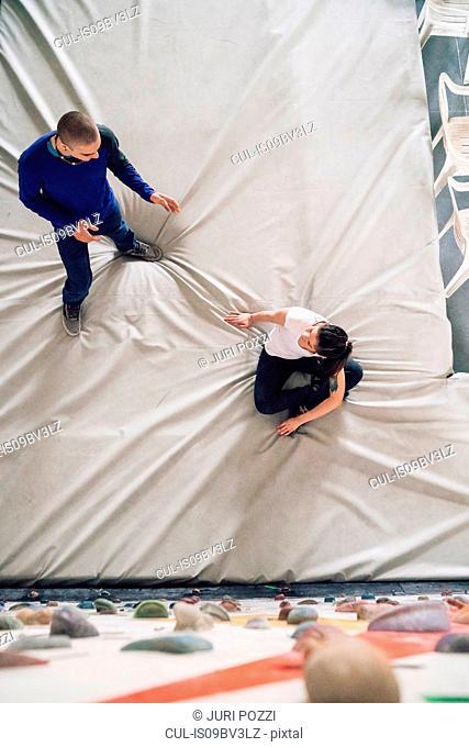 Climber friends talking on crash mat