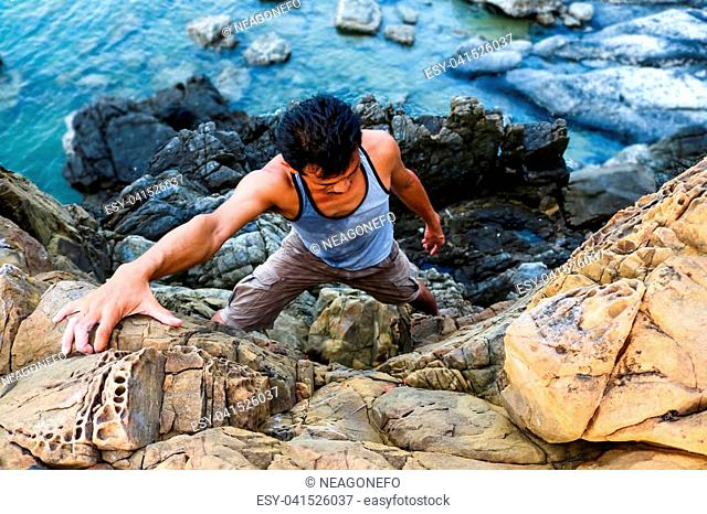 Asian man climbing the rocks near the sea,Ocean background