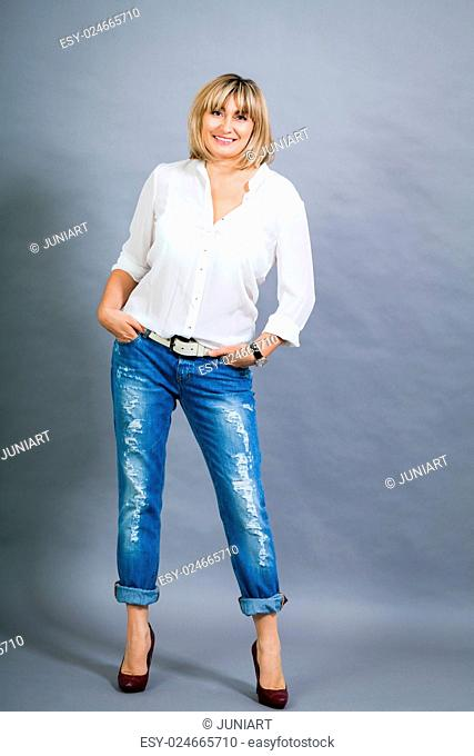 Trendy middle-aged woman with a charming smile and shoulder length blond hair in fashionable modern jeans and high heels posing with her hands in her pockets...