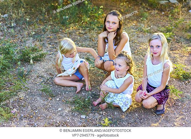 Four infant girls sitting outside on ground in nature garden during sunset. Australian ethnicity. During holiday stay in Hersonissos, Crete, Greece