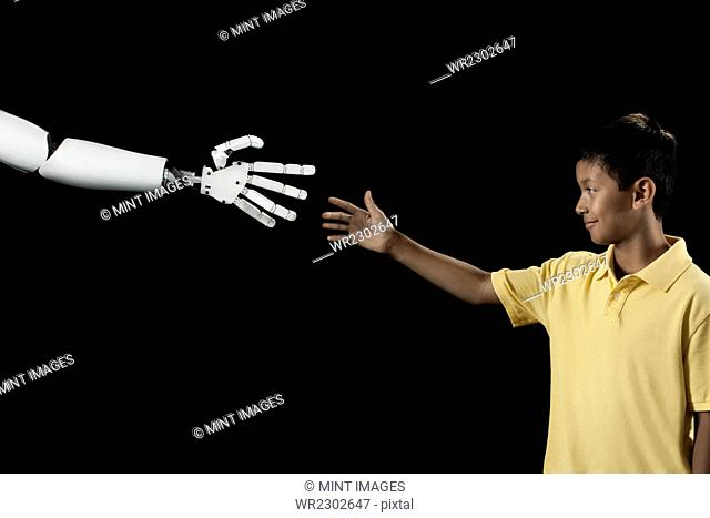 A boy reaching up to touch a robotic hand