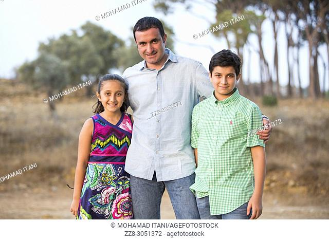 man and his kids standing outdoors smiling