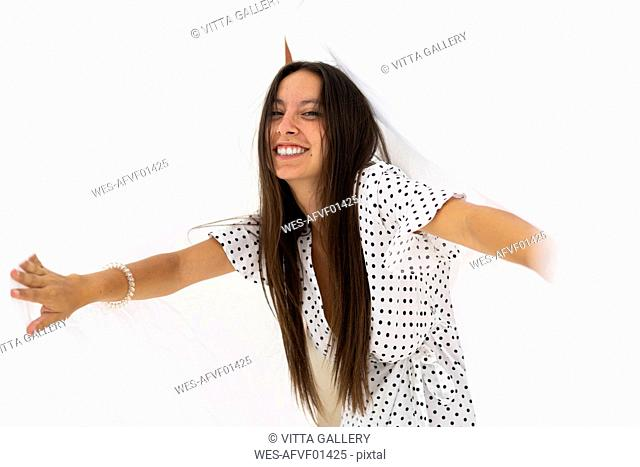 Portrait of young woman having fun with drying bed sheets on roof terrace