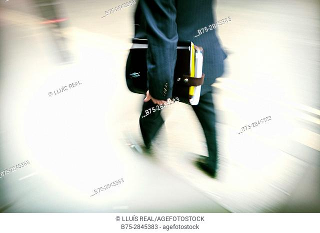 Unrecognizable businessman with portfolio walking on the street. London, England