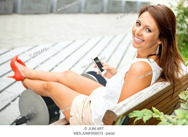 Portrait of smiling young woman sitting on a bench with her smartphone