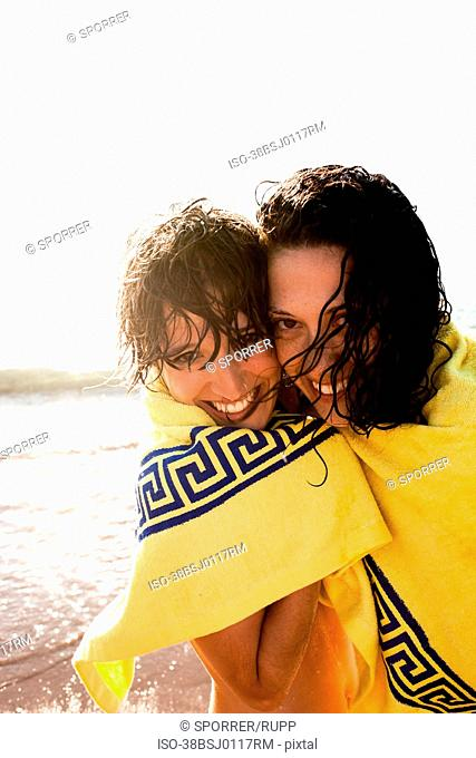 Women huddled in towel on beach