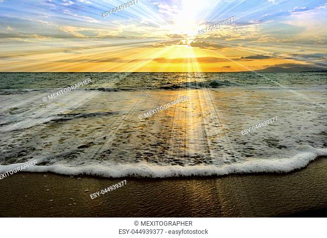 Ocean sunset rays is an ethereal ocean scenic with sun beams bursting forth from the setting sun as a gentle wave comes to shore
