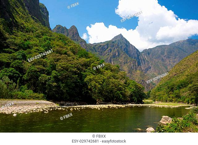 Machu Picchu archeological site viewed on the top in the background from the valley of Urubamba River, covered by lush green jungle