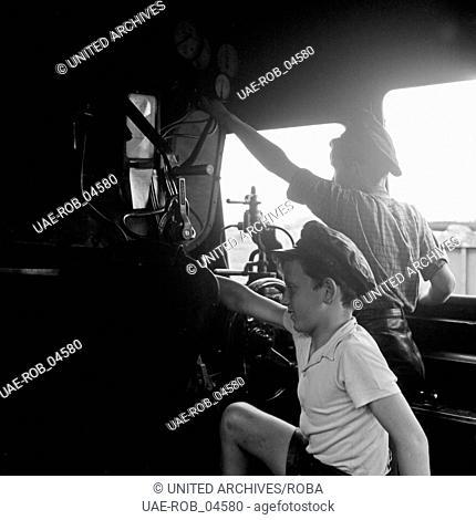 Zwei Jungen spielen Lokführer im Führerhaus einer Dampflokomotive, Deutschland 1950er Jahre. Two boys playing locomotive driver at the driver's cab of a steam...