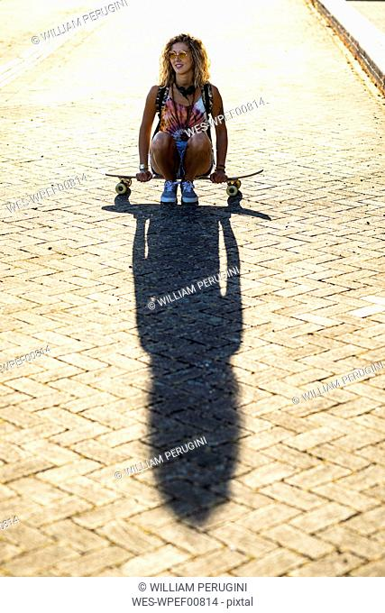Young woman sitting on a skateboard in sunlight