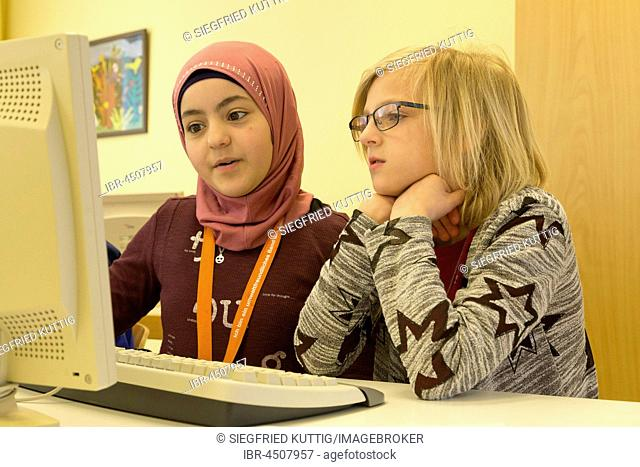 Elementary school girls working on computers in computer room, Lower Saxony, Germany
