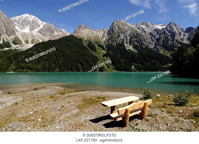 Bench and table at the bank of Antholzer lake in the sunlight, Val Pusteria, South Tyrol, Italy, Europe