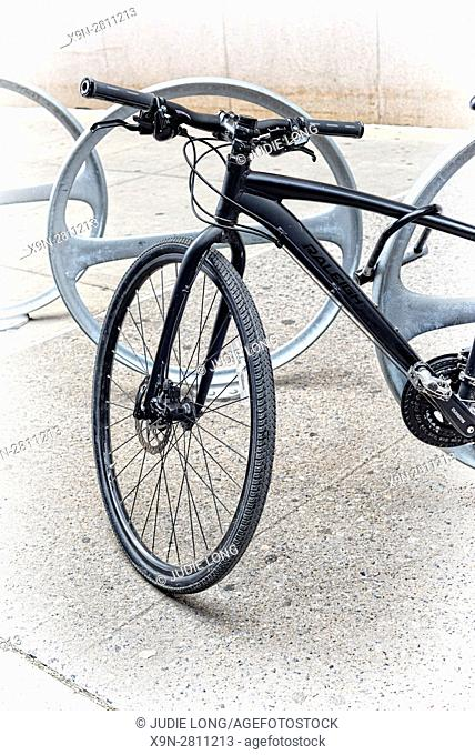 Black Racing Type Bicycle Locked to a Bike Parking Station on a Manhattan, New York City Sidewalk